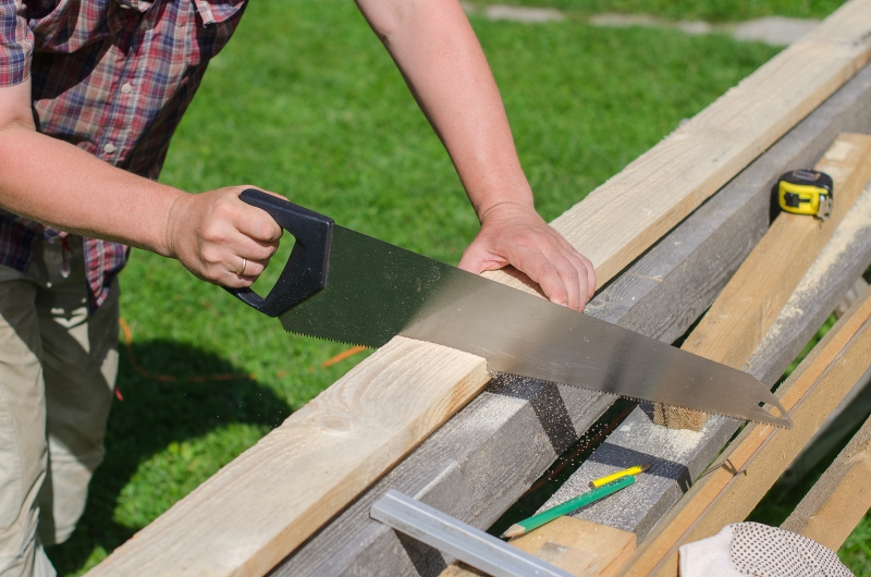 5900154-handyman-sawing-long-wooden-plank-outdoors
